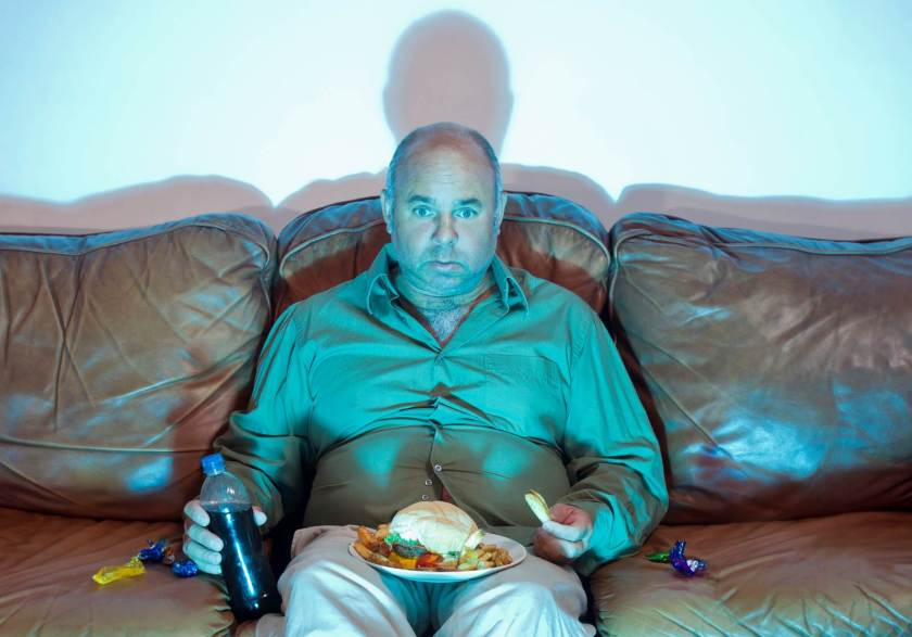 636007806146880820-1559995890_a-mature-overweight-man-sitting-on-an-old-couch-watching-tv-with-an-unhealthy-meal-of-hamburger-french-fries-and-soda-pop-2.jpg